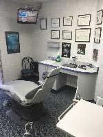 Dr. Michael Dab examination room with a tv and dental accolades on the wall